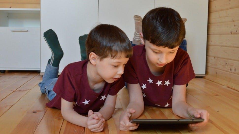Zwei Kinder liegen auf dem Boden und spielen mit einem Tablet für Kinder