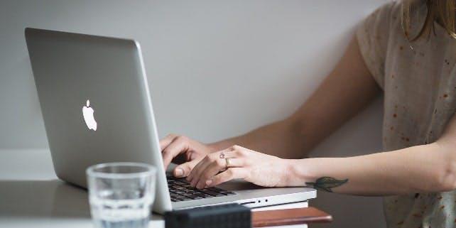 Frau schreibt auf ihrem Laptop