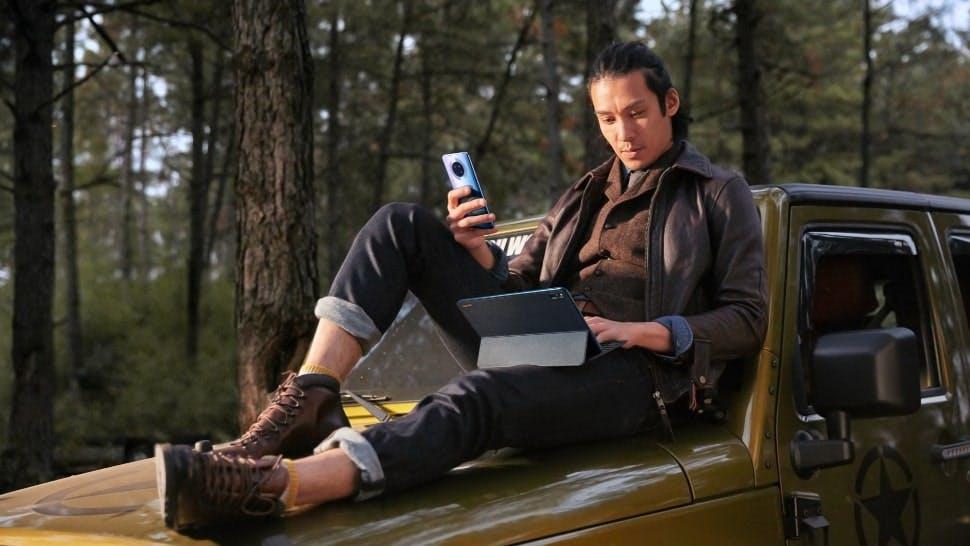 Mann sitzt mit HUAWEI Smartphone und HUAWEI MatePad auf einem gelben Auto im Wald