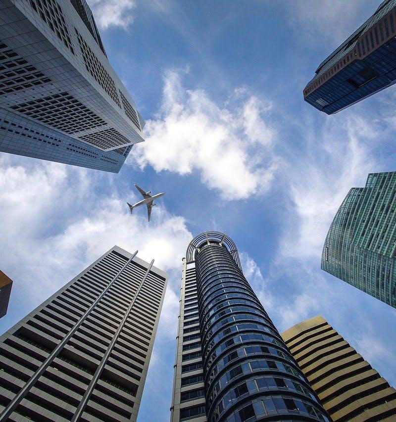 Wolkenkratzer, die in den Himmel ragen und Flugzeug in der Luft.