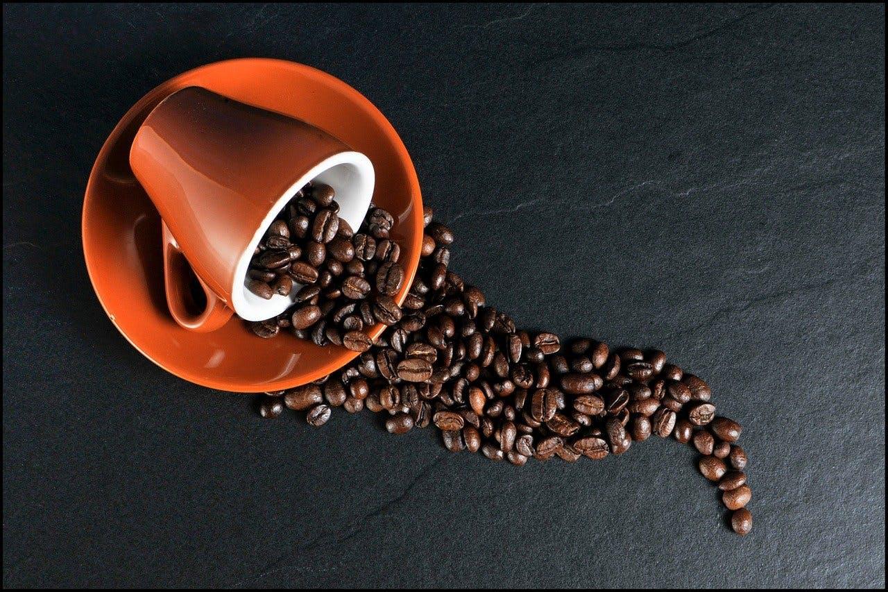 Kaffeetasse voller Kaffeebohnen liegt umgekippt auf Unterteller