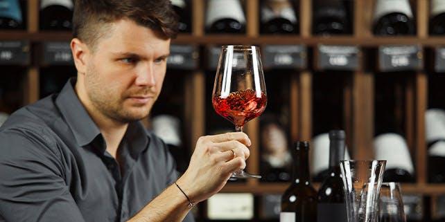 Männ hält Weinglas hoch und schaut sich den Inhalt genau an