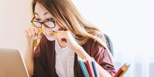 Eine Frau ist beim Verzweifeln und beißt in einen Bleistift