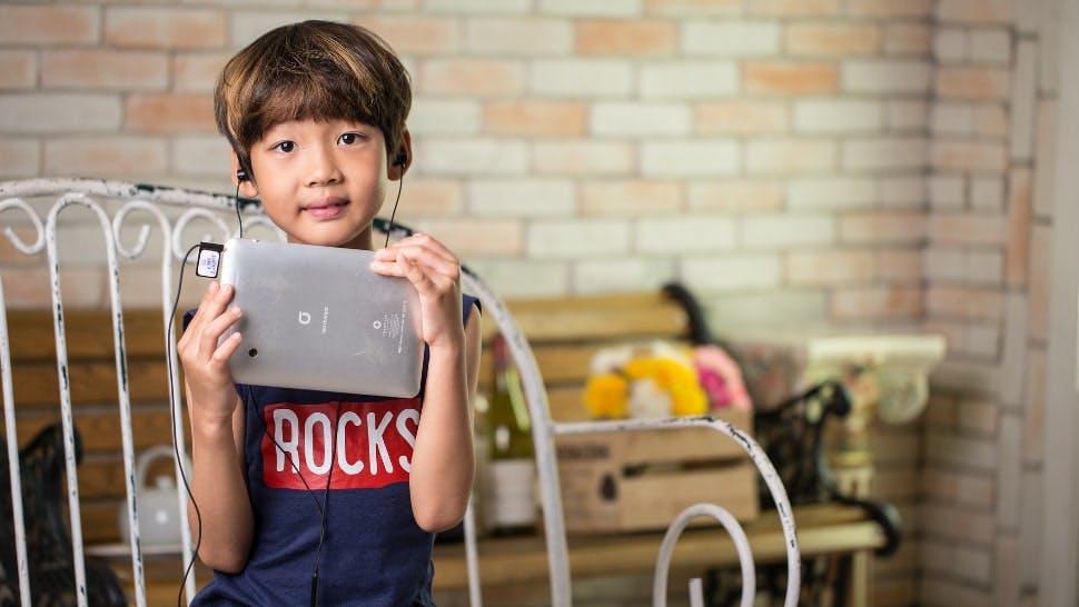 Ein Kind sitzt auf einer Bank und hat ein Tablet für Kinder in seinen Händen