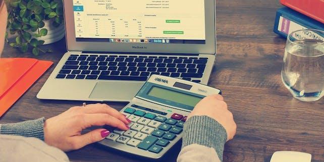 Frau sitzt mit einem Taschenrechner vorm Laptop und macht ihre Steuererklärung
