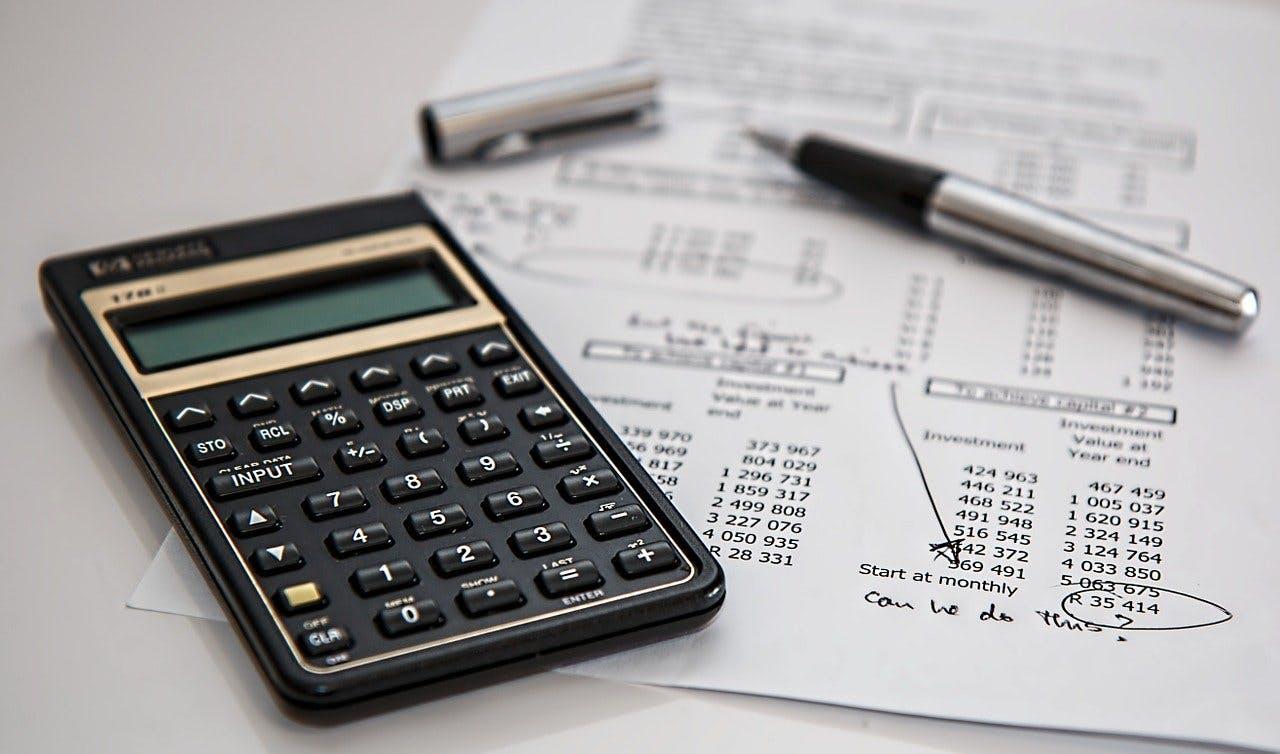 Taschenrechner und Kugelschreiber liegen auf Blatt Papier mit vielen Zahlen darauf