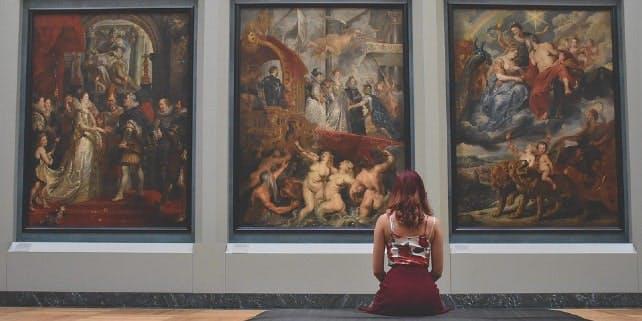 Frau sitzt in Museum und schaut sitzend drei Bilder an