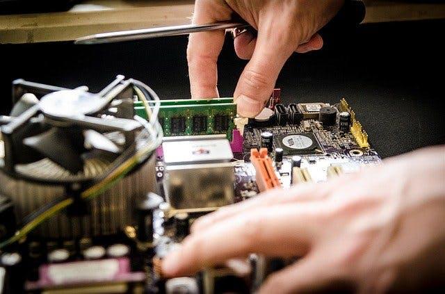 Zwei Hände arbeiten mit Schraubenzieher an Computer-Mainboard.