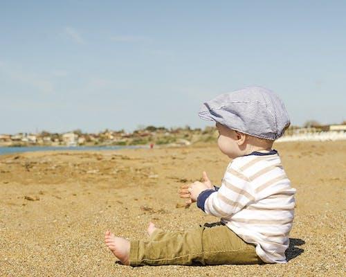 Kleiner Junge sitzt am Strand