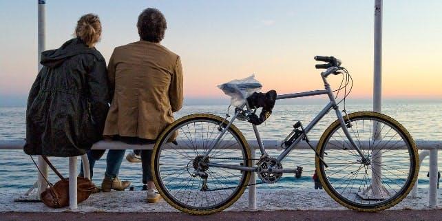 Eine Frau und ein Mann genießen die Aussicht aufs Meer und neben ihnen steht ein abgeschlossenes Fahrrad