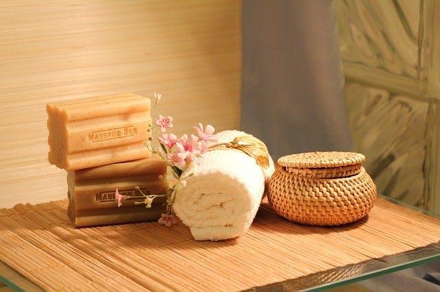 Seifenstücke und Handtuchrolle auf Bambusmatte.