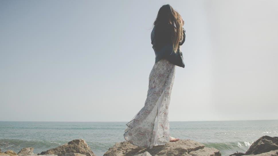 Frau in langem Sommerkleid steht auf einem Felsen und guckt Richtung Meer