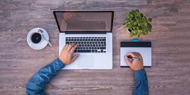 Mann arbeitet an seinem Laptop und macht sich Notizen