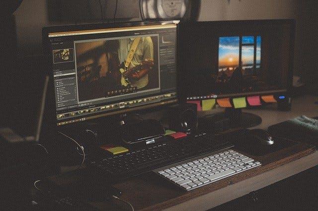 Workstation mit zwei Bildschirmen und laufendem Videobearbeitungsprogramm.