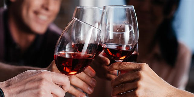 Vier Leute stoßen mit einem Glas Rotwein an