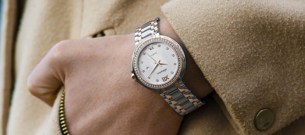 Nahaufnahme von einer angelegten silbernen Uhr mit goldenen Details