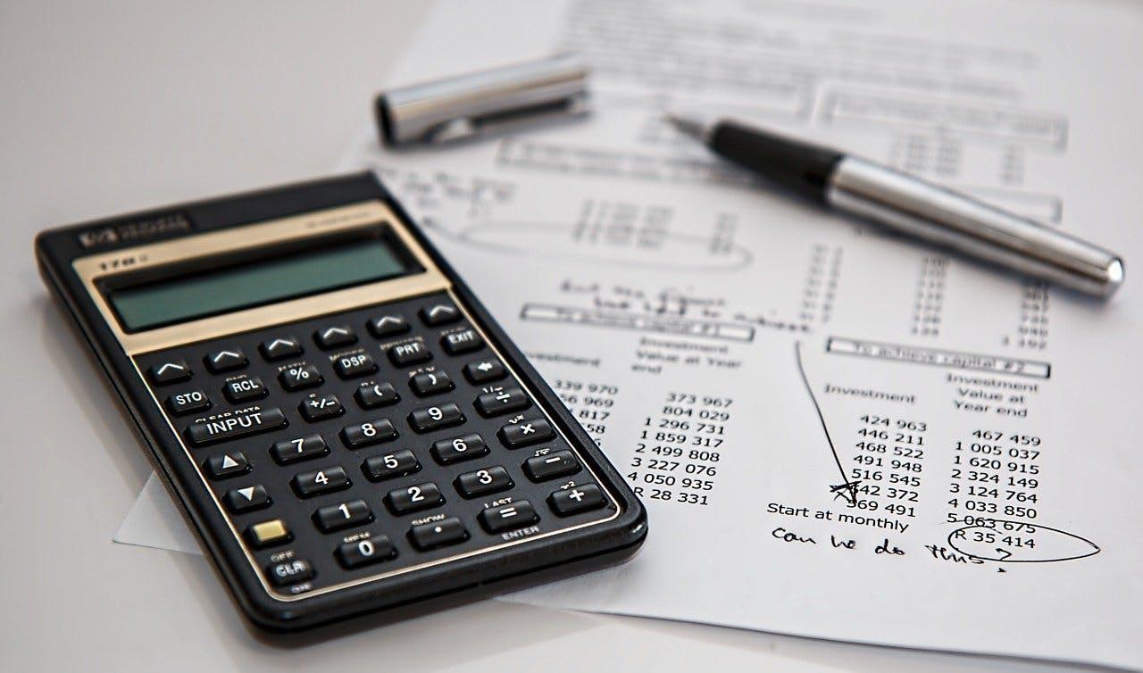 Taschenrechner und Kugelschreiber liegen auf Versicherungsunterlagen