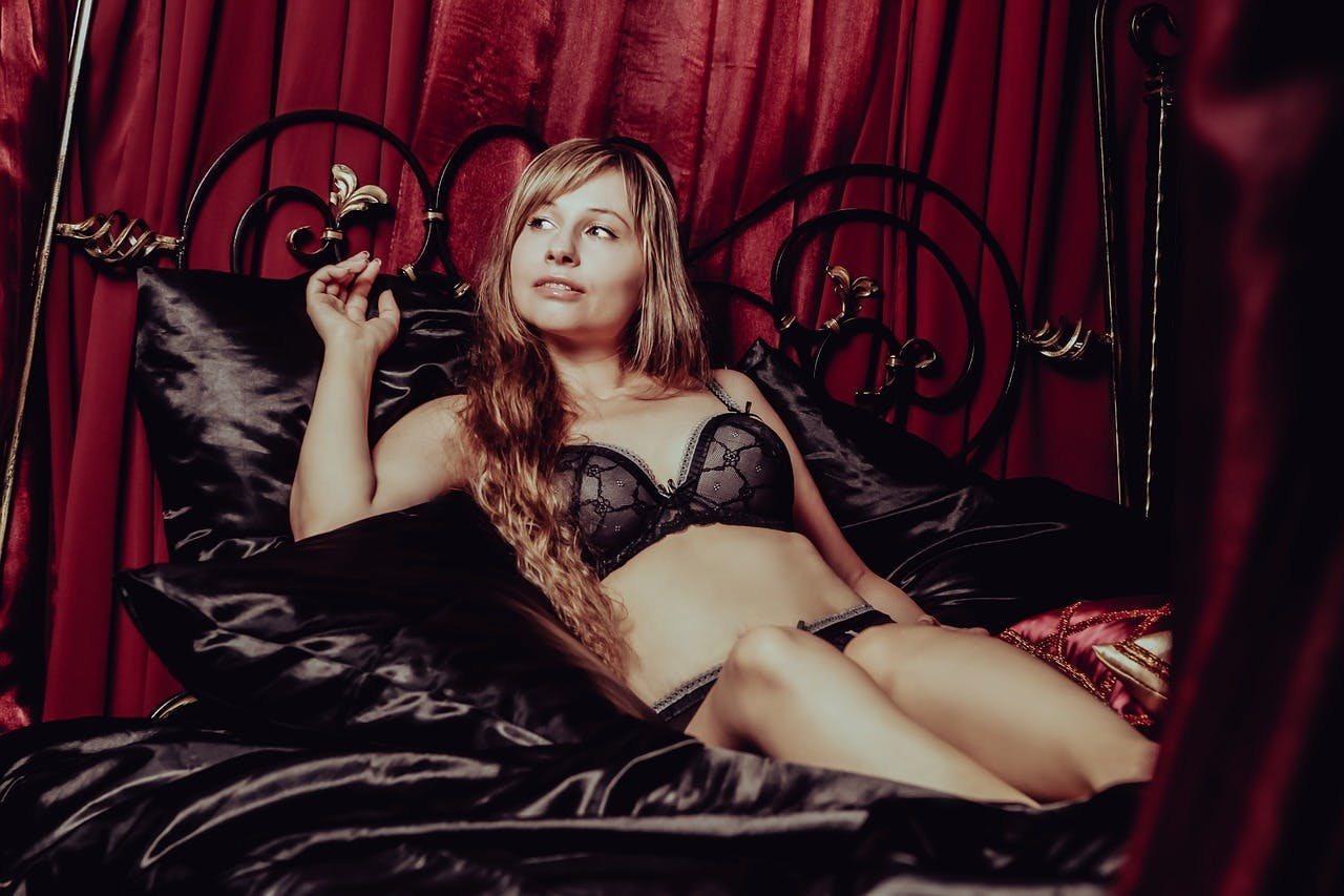 Frau liegt im Bett und trägt schwarze Unterwäsche von Triumph