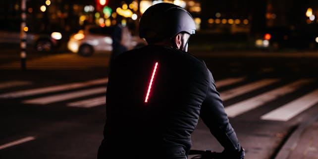 Radfahrer im Dunkeln mit LED-Streifen auf dem Rücken