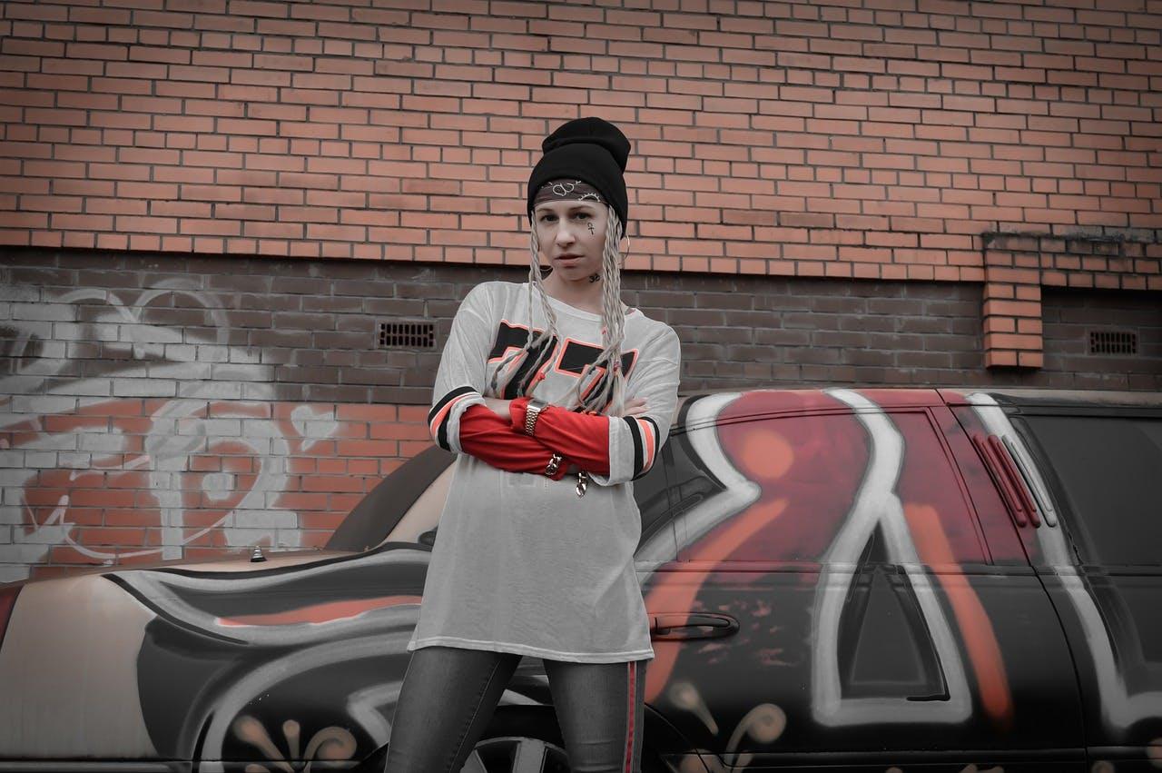 Frau in Streetwear Bekleidung steht vor einer mit Graffiti besprühten Wand
