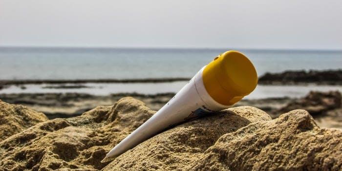Tube Sonnencreme liegt im Sand am Meer