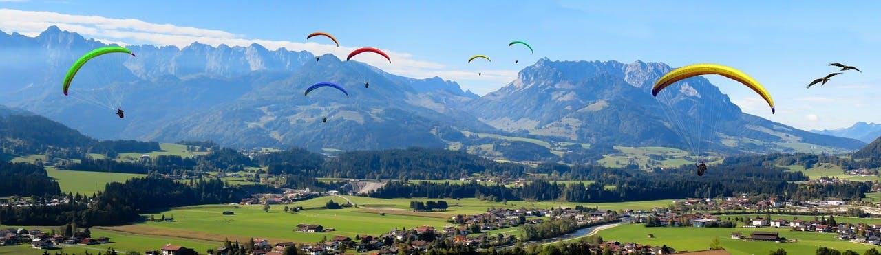 Mehrere Paraglider fliegen über Alpental