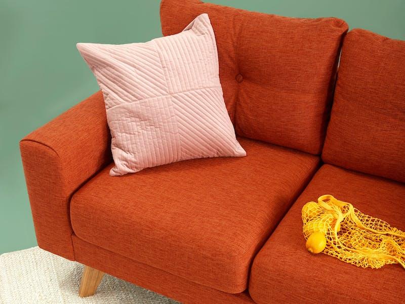 Hellrotes Sofa mit rosa Kissen