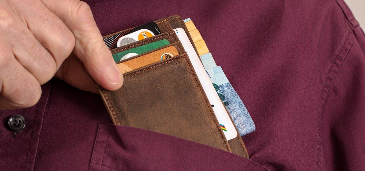 Mann zückt Brieftasche aus der Brusttasche seines Hemdes