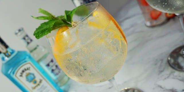 Gin Getränk mit einem Minzblatt und Orangenscheiben