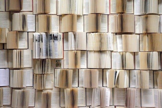 Bücherwand mit aufgeklappten Büchern