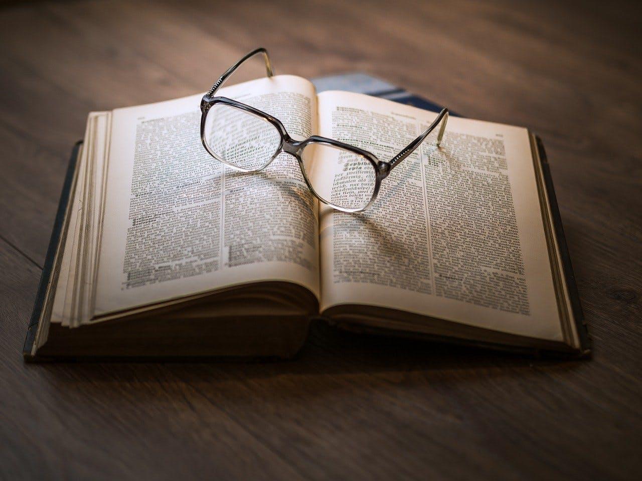 Brille liegt auf aufgeschlagenem Buch