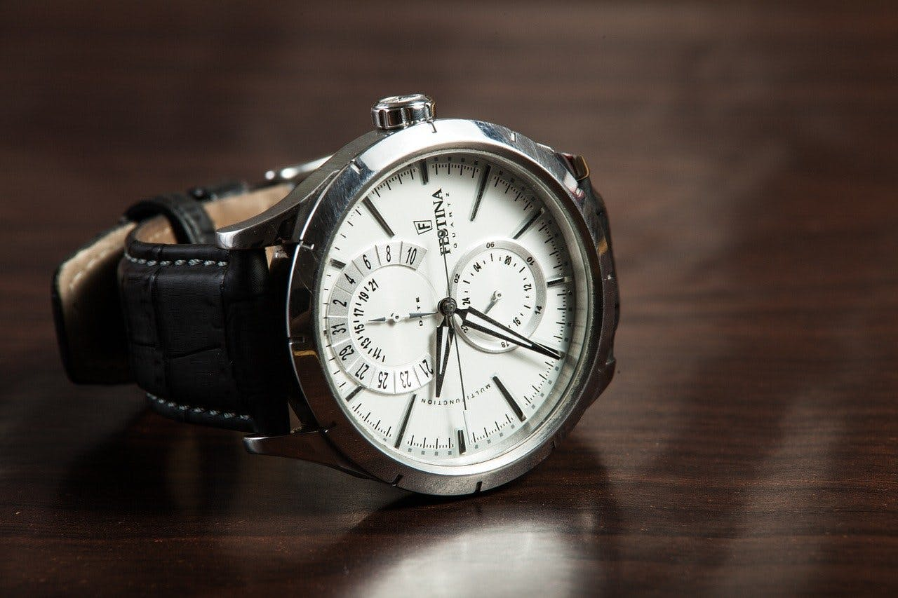 Silberne Armbanduhr mit weißem Ziffernblatt und zwei Komplikationen