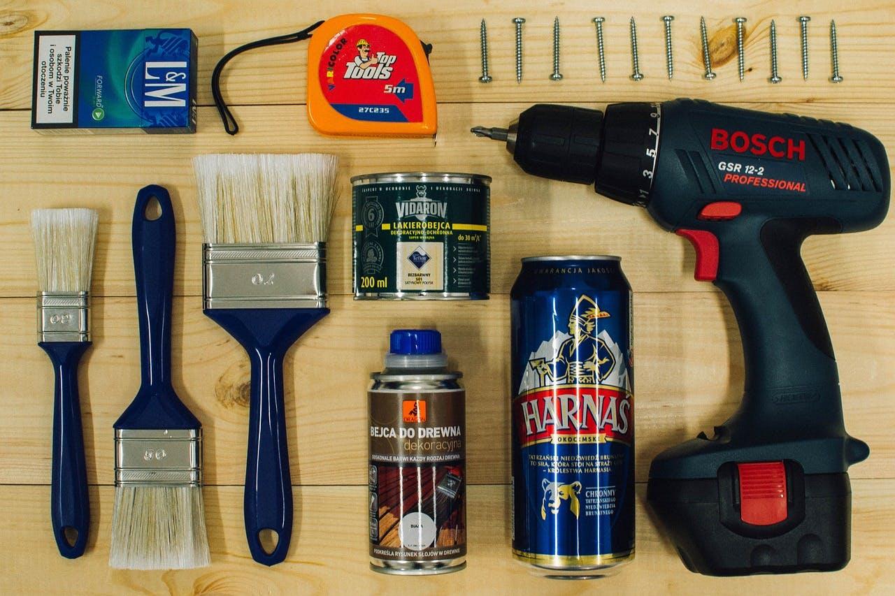 Bosch Bohrmaschine, Lack, Schrauben, Pinsel, Massband und Zigaretten rechtwinklig zueinander angeordnet auf einer Holzplatte liegend