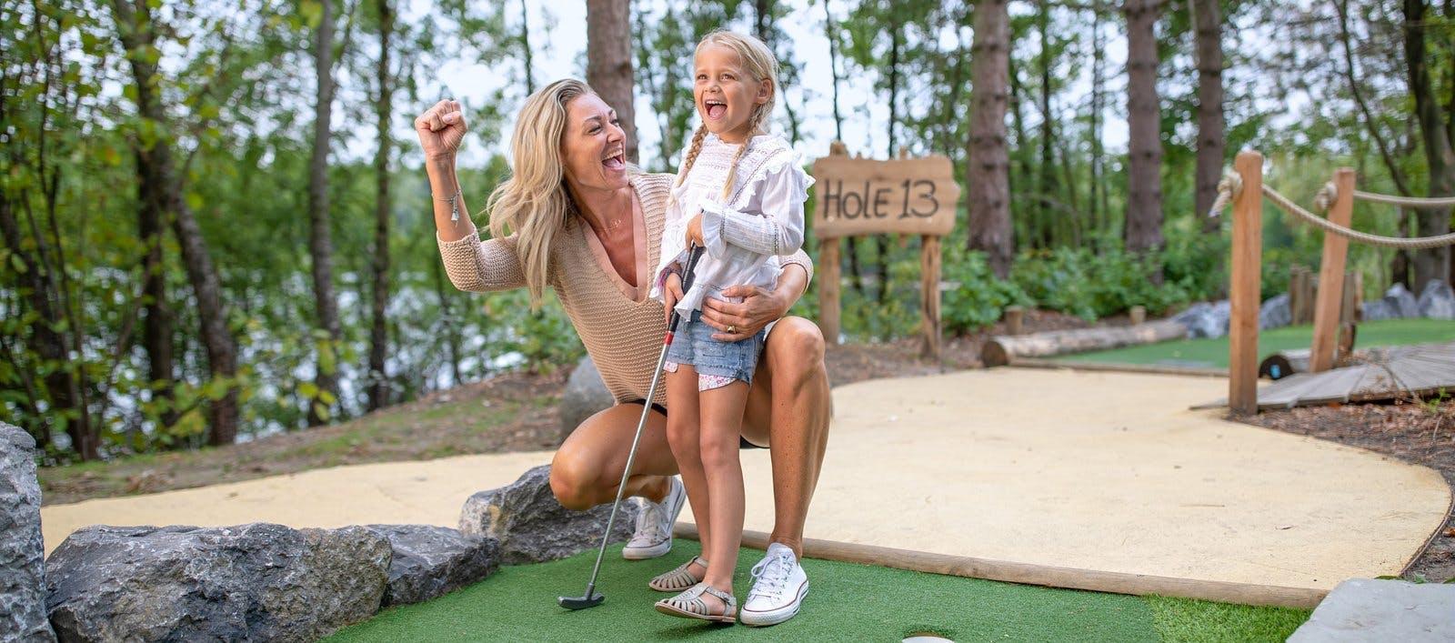 Mutter spielt Mini-Golf mit Ihrer Tochter