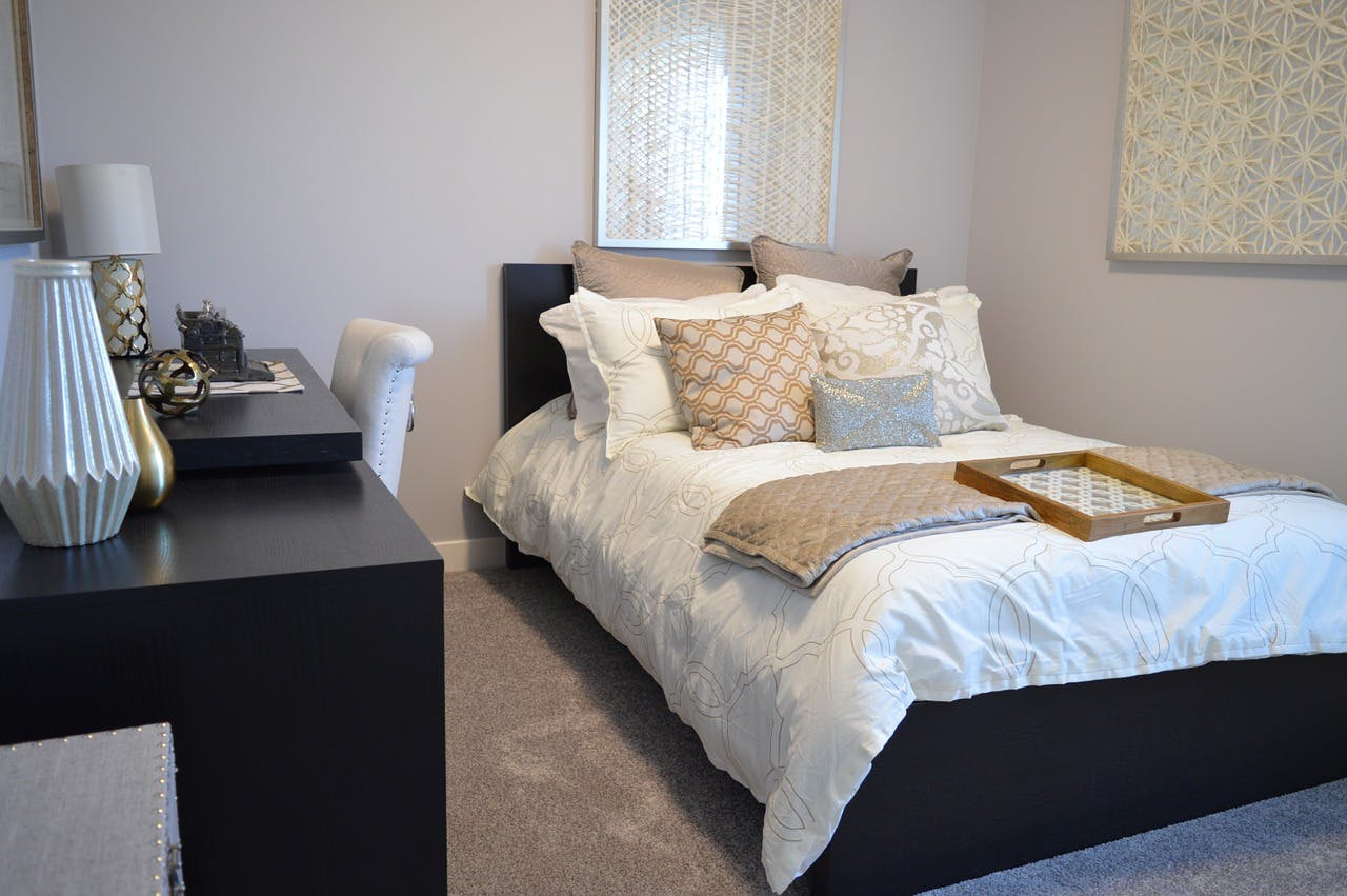 Schlafzimmer mit Bett und vielen Kissen sowie einem dunklen Sideboard