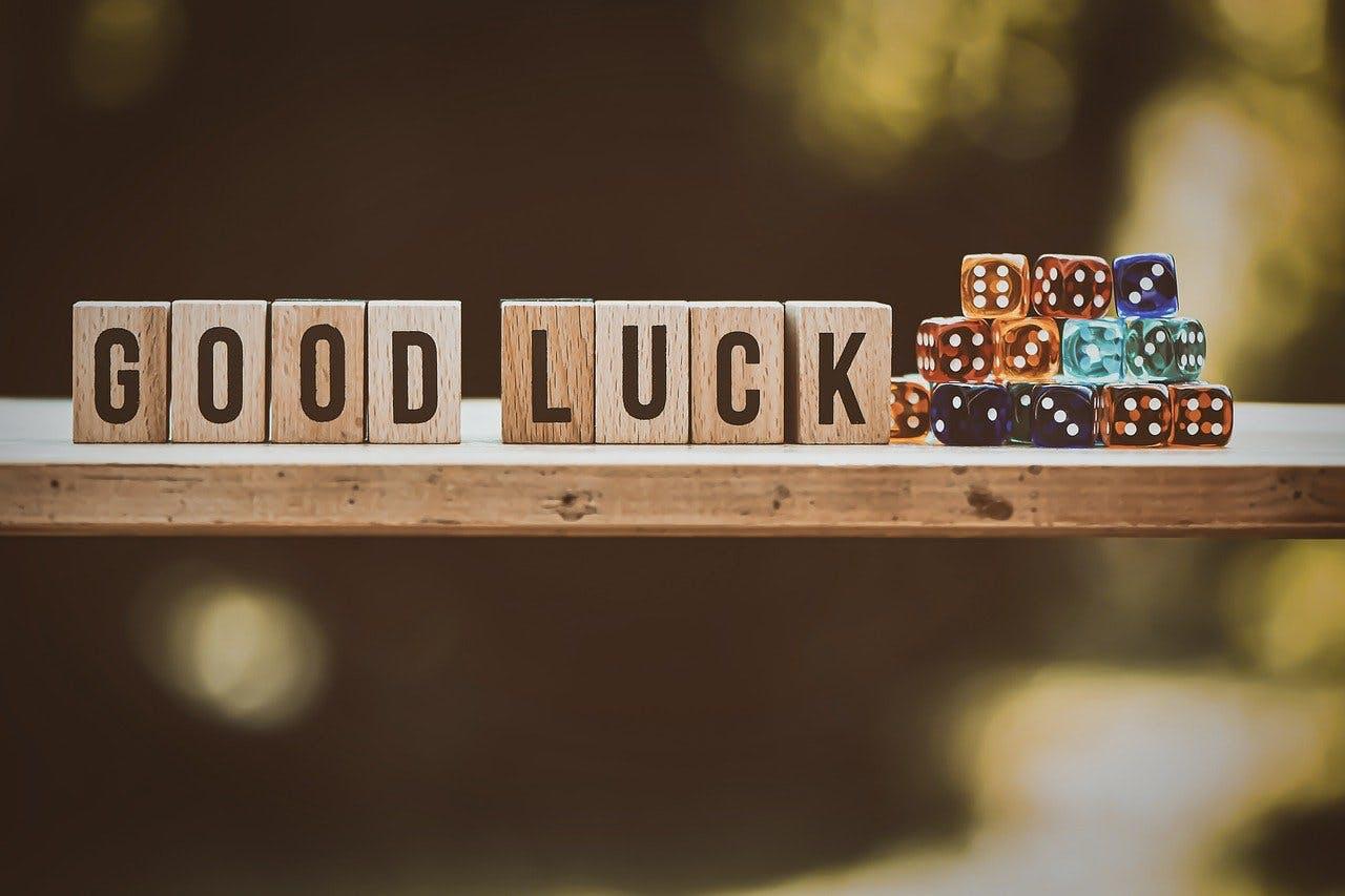 """Waagerechtes Brett, auf dem Holzwürfel mit der Aufschrift """"Good Luck"""" und herkömmliche Spielwürfel in verschiedenen Farben drapiert sind"""