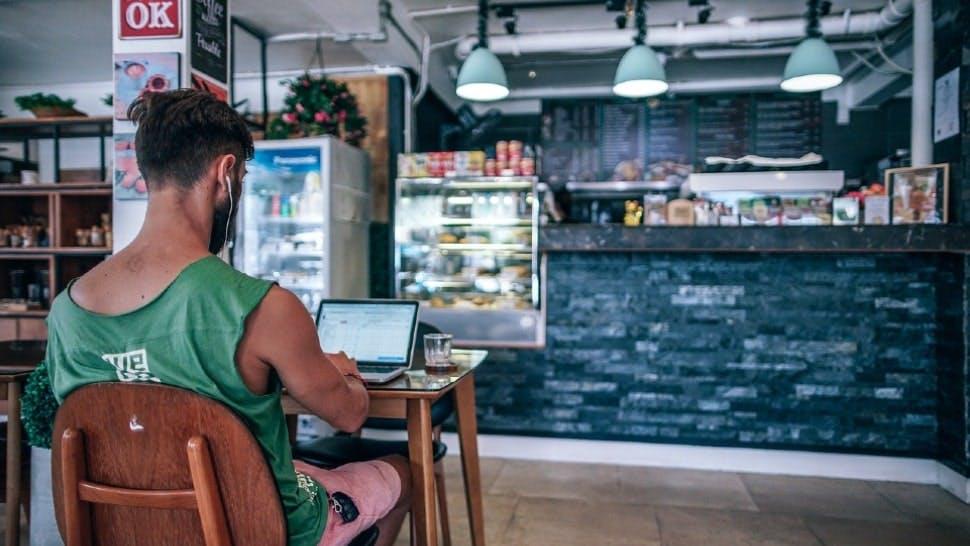 Ein Mann sitzt vor einem Laptop in einem Cafe