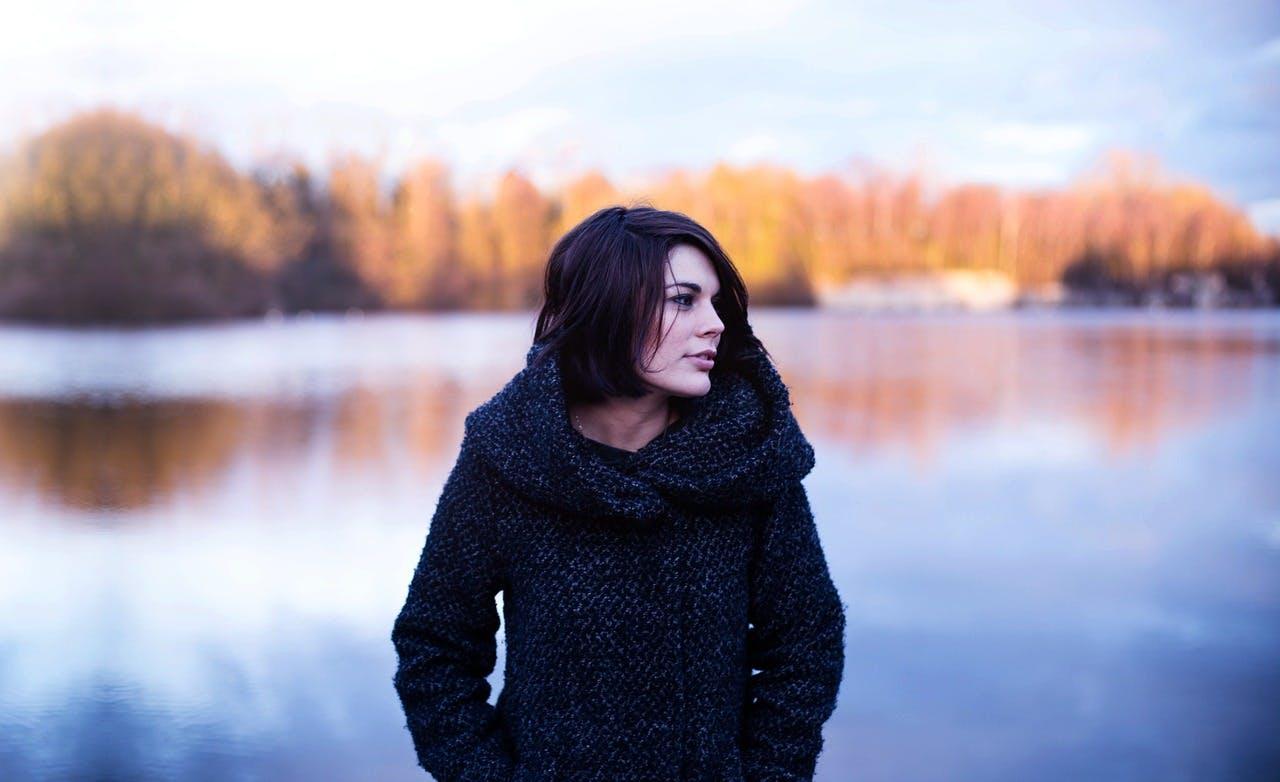 Frau in stylishem Mantel spaziert im Herbst an einem See