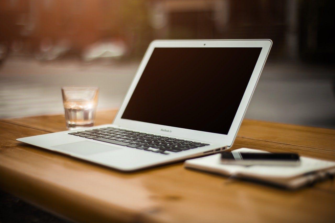 Laptop steht aufgeklappt auf einem Tisch
