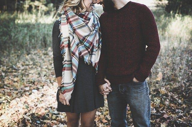 Paar hält Händchen. Modisch gekleidet