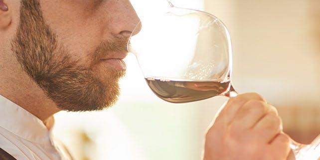 Mann riecht an dem Wein in seinem Glas