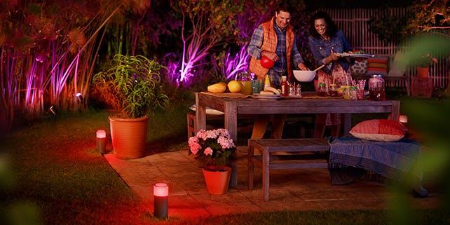 Paar holt sich Essen am Tisch im Garten, rundherum pinkes Licht
