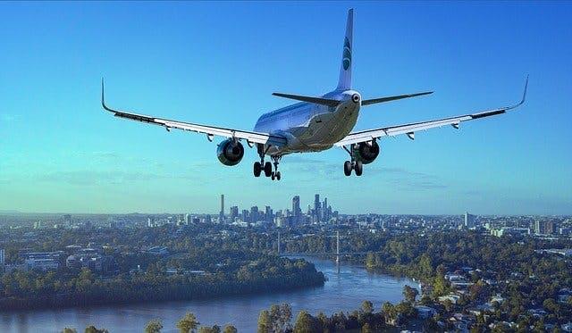 Landendes Passagierflugzeug über Großstadt.