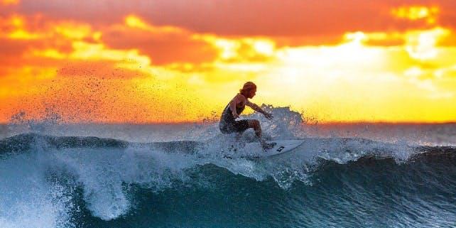 Mann surft bei wunderschönen Abendröte