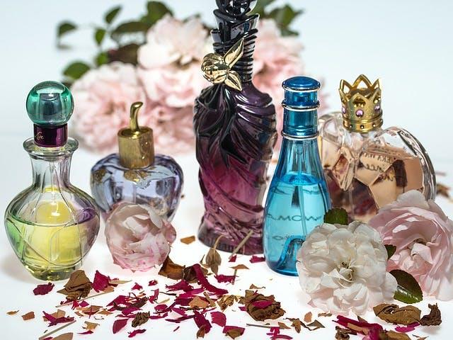 Parfum-Flakons zwischen Blüten.