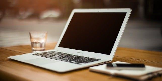 Ein MacBook steht zwischen einem Notizbuch und einem Glas Wasser