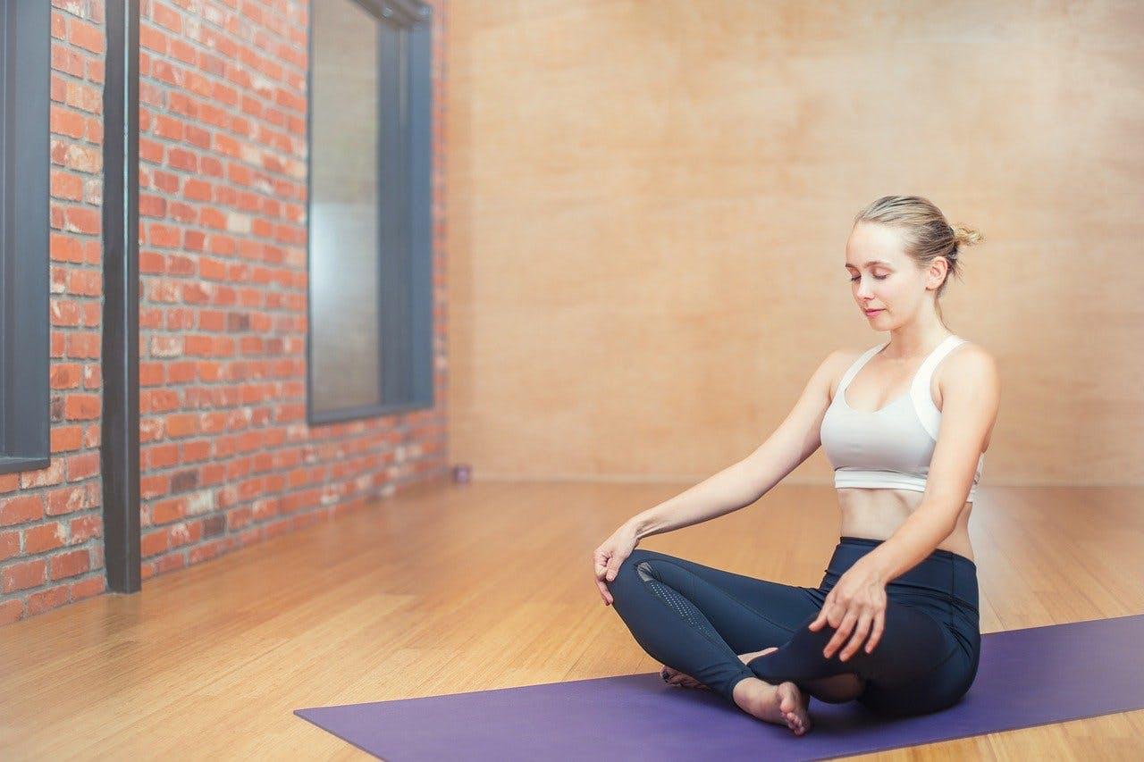 Frau sitzt im Schneidersatz in einem Yogastudium auf einer lila Yogamatte und meditiert