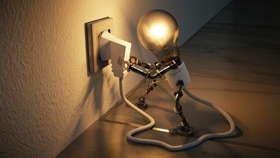 Glühbirne steckt Stecker ein - so geht Energiesparen im Haushalt