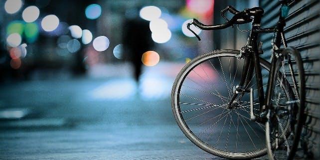 Ein Rennrad lehnt an der Wand in der Nacht