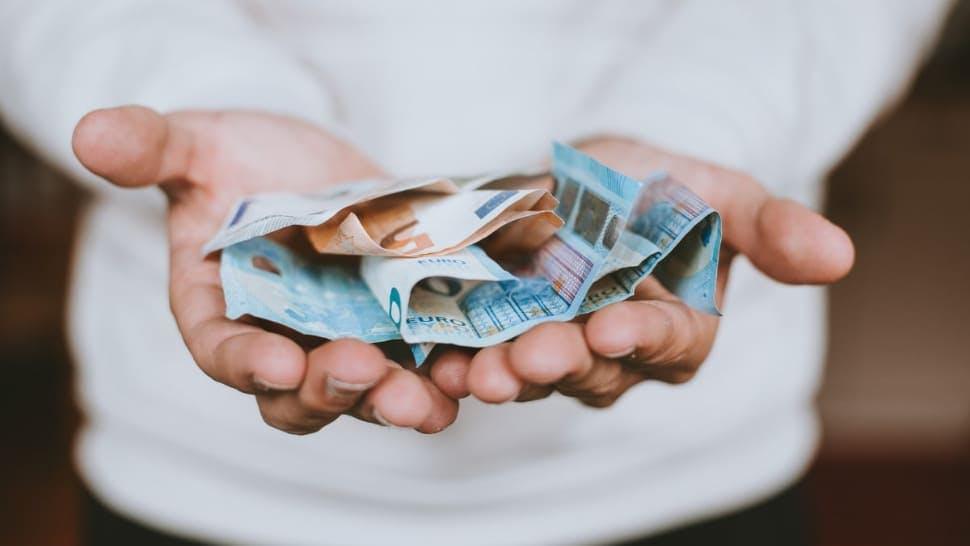 Geöffnete Hände mit Geldscheinen